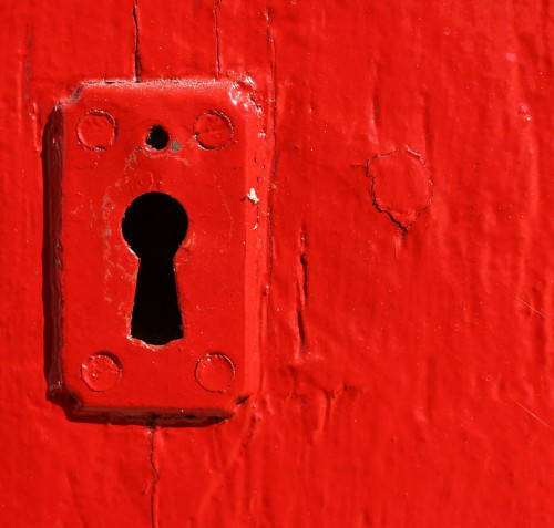 Photograph of a keyhole in a red painted door