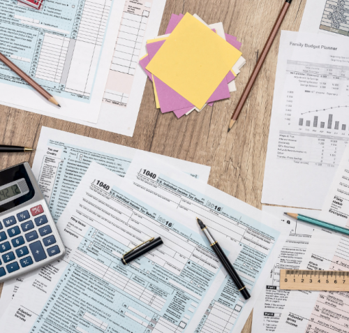 A desk picturing banking statements, tax forms, notes, pencils, and calculators.
