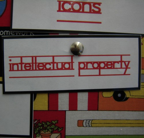 "Photograph of a bulletin board with a paper with the words ""intellectual property"" pinned to it."