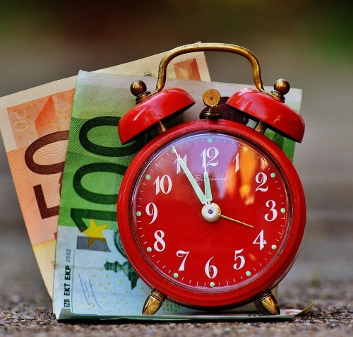 Red clock in front of currency
