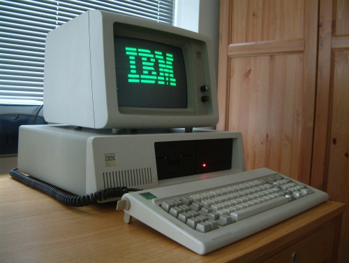 "Photograph of an old personal computer with ""IBM"" in green letters on the screen."