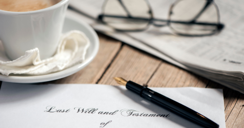The top portion of a last will and testament pictured alongside a ink pen, coffee cup, and reading glasses.